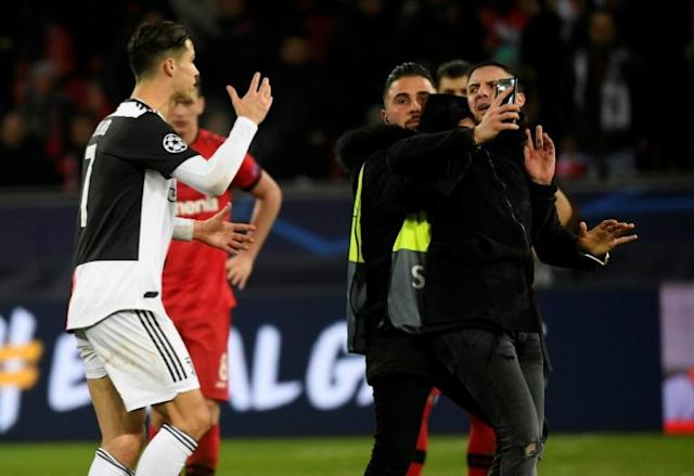 Close call: Cristiano Ronaldo berates a pitch invader who wanted a selfie with the Juventus star (AFP Photo/INA FASSBENDER)