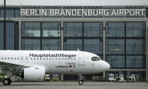 A 'Lufthansa' ariplane is parked in front of Terminal 1 after its arrival at the new Berlin-Brandenburg-Airport 'Willy Brandt' in Berlin, Germany, Saturday, Oct. 31, 2020. Berlin's new airport opens after years of delays and cost overruns. (AP Photo/Michael Sohn)