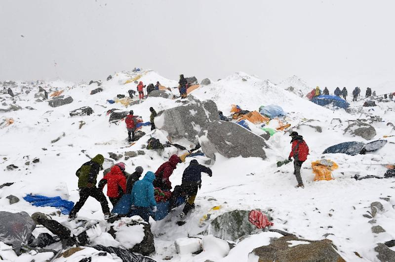 Sherpas and climbers help carry a person injured by an avalanche that flattened part of Everest Base Camp, on April 25, 2015 (AFP Photo/Roberto Schmidt)