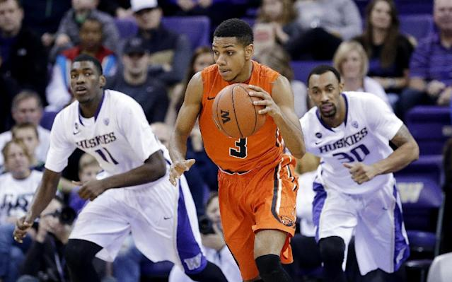 Hallice Cooke (3) drives up court as Washington's Mike Anderson, left, and Desmond Simmons in the first half of an NCAA college basketball game Saturday, Jan. 25, 2014, in Seattle. Washington won 87-81. (AP Photo/Elaine Thompson)