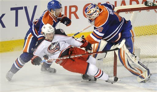 Edmonton Oilers goalie Devan Dubnyk, right, pushes Columbus Blue Jackets' Ryan Russell into Edmonton's Nick Schultz during the second period of an NHL hockey game Wednesday, March 14, 2012, in Edmonton, Alberta. (AP Photo/The Canadian Press, John Ulan)