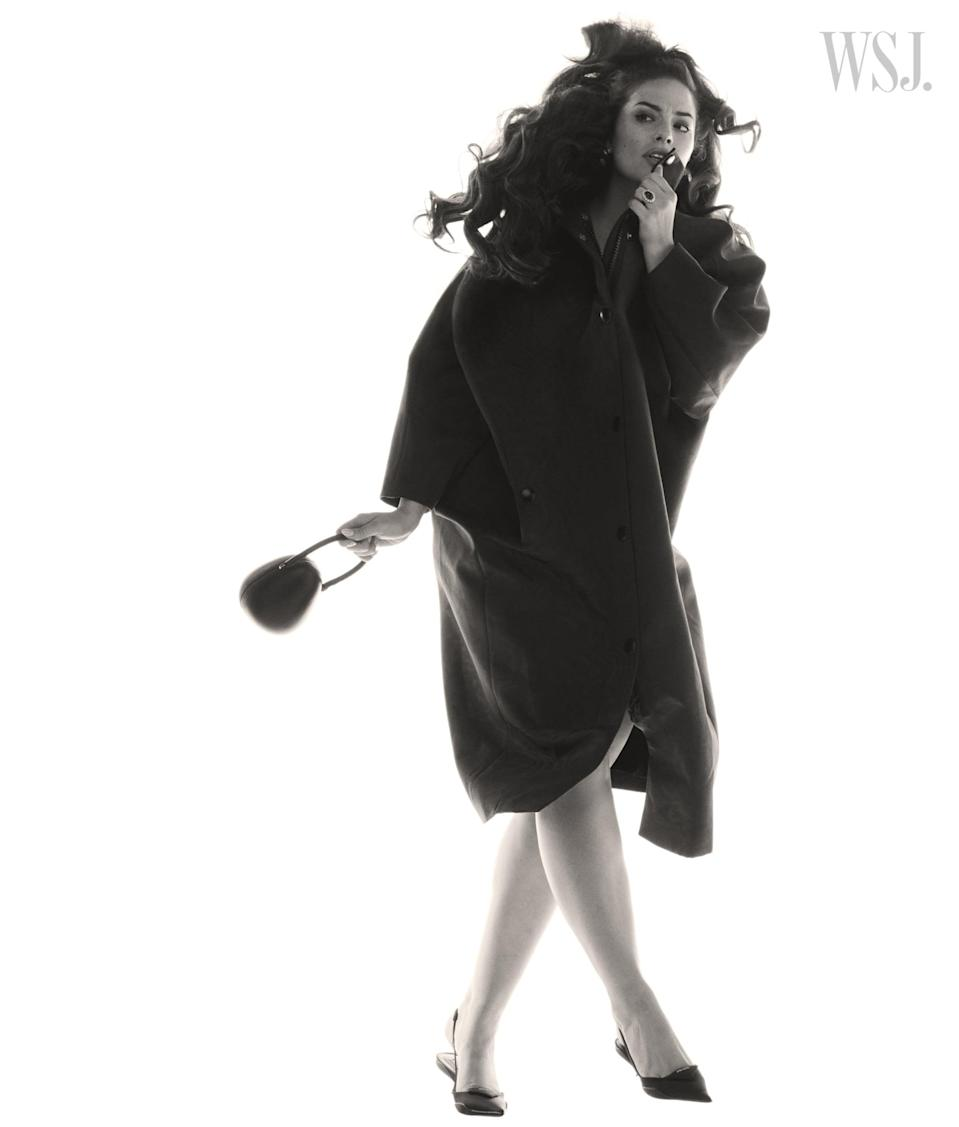 <p>Ashley wearing a Prada coat and heels, a Simone Rocha bag, Kenneth Jay Lane earrings, and a Ben-Amun by Isaac Manevitz ring.</p>