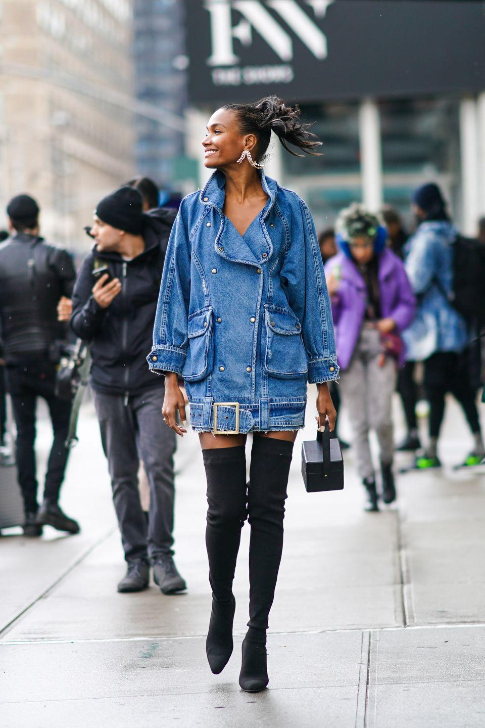 <p>A denim mini with black thigh-high boots looks way stylish—especially with statement earrings and a geometric top-handle bag. </p>
