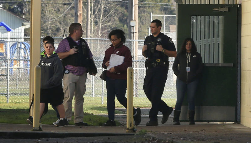 Eugene Police officers escort children from Cascade Middle School in Eugene, Ore., following an officer-involved shooting outside the school Friday, Jan. 11, 2019. (Chris Pietsch/The Register-Guard via AP)