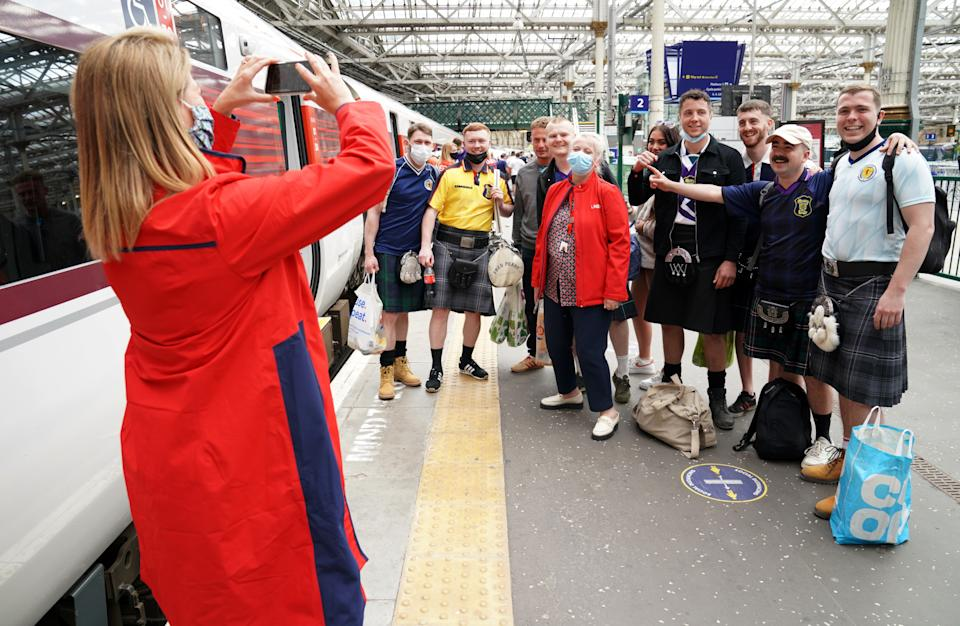 Scotland fans have their picture taken with and LNER staff member at Edinburgh Waverley railway station as they prepare to travel to London ahead of the UEFA Euro 2020 match between England and Scotland at Wembley Stadium. Issue date: Friday June 18, 2021. (Photo by Jane Barlow/PA Images via Getty Images)