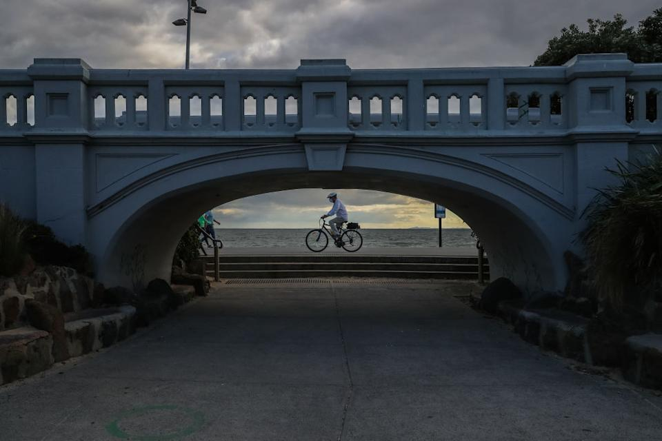 A person cycles along St Kilda beach on August 21, 2021 in Melbourne, Australia.