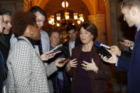 "Sen. Amy Klobuchar, D-Minn., center, talks to reporters as she arrives at the Capitol in Washington, Wednesday, Jan. 22, 2020. The U.S. Senate plunges into President Donald Trump's impeachment trial with Republicans abruptly abandoning plans to cram opening arguments into two days but solidly rejecting for now Democratic demands for more witnesses to expose what they deem Trump's ""trifecta"" of offenses. Trump himself claims he wants top aides to testify, but qualified that by suggesting there were ""national security"" concerns to allowing their testimony. (AP Photo/Julio Cortez)"