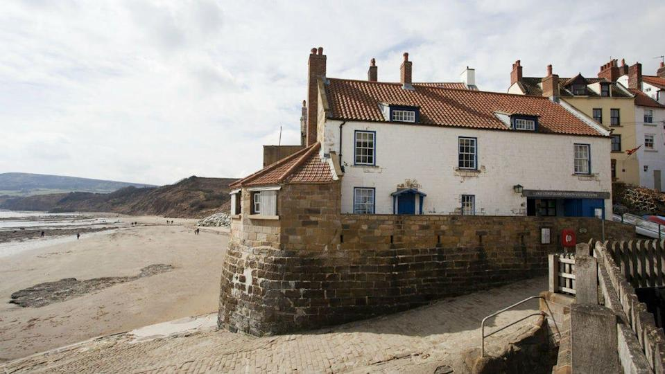 """<p>Formerly an old coastguard station, this spot is located on the top of the sea wall of one of North Yorkshire's most famous coastlines. Perfectly sized for two people, the coastal cottage is made up of a one-bedroom loft, an open plan kitchen, a bathroom and a dining area with sea views. </p><p>It's located in Robin Hood's Bay – a 17th Century fishing village – which is the perfect place to stay if you fancy taking part in the Coast to Cast Walk which ends just nearby the Boatman's Loft. Whitby is located just a six mile walk away along the clifftops. </p><p><strong>Loft for 2 from £266 per night</strong></p><p><a class=""""link rapid-noclick-resp"""" href=""""https://go.redirectingat.com?id=127X1599956&url=https%3A%2F%2Fwww.nationaltrust.org.uk%2Fholidays%2Fboatmans-loft-formerly-old-coastguard-station-yorkshire&sref=https%3A%2F%2Fwww.elle.com%2Fuk%2Flife-and-culture%2Fculture%2Fg33261665%2Fcoastal-cottages%2F"""" rel=""""nofollow noopener"""" target=""""_blank"""" data-ylk=""""slk:BOOK ONLINE"""">BOOK ONLINE</a></p>"""