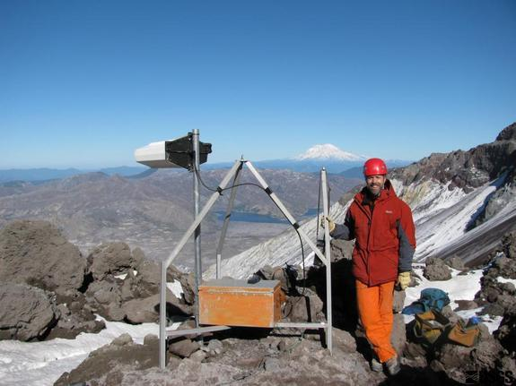 Installing an earthquake monitor at the summit of Mount St. Helens in Washington. Mount Rainier is in the background.