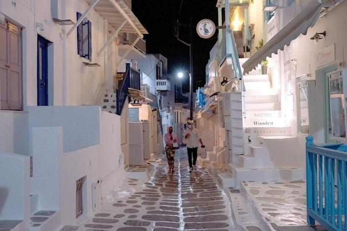 Pedestrians walk along an empty street in the evening ahead of the return of tourists in Mykonos, Greece, on Sunday, May 9, 2021.
