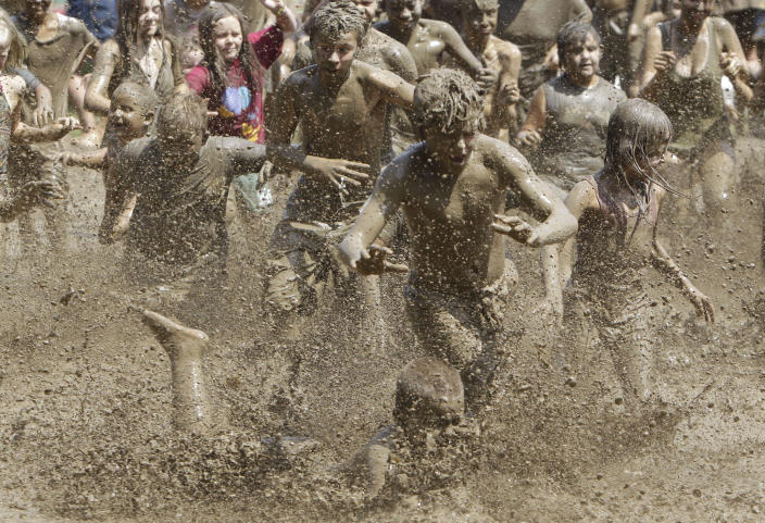 Kids run into the mud pit during the annual Mud Day in Westland, Mich., Tuesday, July 12, 2011. Wayne County mixes more than 200 tons of topsoil and over 20,000 gallons of water to ensure that the mud is just right. (AP Photo/Carlos Osorio)