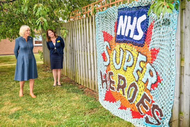 The Duchess of Cornwall is shown a knitted tribute to NHS staff by Gloucestershire Hospitals NHS Foundation CEO Deborah Lee. (PA Images)