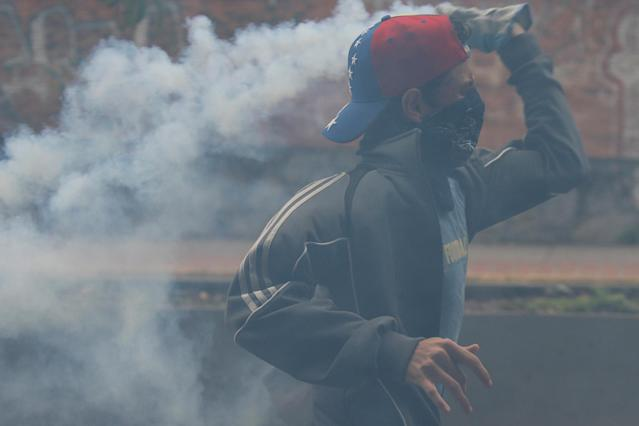 <p>A demonstrator throws back a tear gas canister during a protest against Venezuela's President Nicolas Maduro's government in Caracas, Venezuela May 2, 2017. (Photo: Carlos Garcia Rawlins/Reuters) </p>