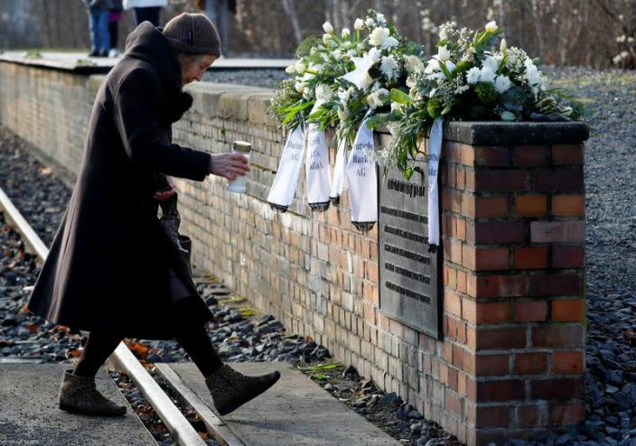 A woman places a candle at the Gleis 17 (Platform 17) memorial at Berlin-Grunewald train station in Berlin