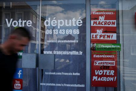 "A man walks past the local headquarters of Francois Ruffin, a member of parliament of political party "" La France Insoumise"" (France Unbowed), in Amiens, France, May 16, 2019. Picture taken May 16, 2019.  REUTERS/Pascal Rossignol"