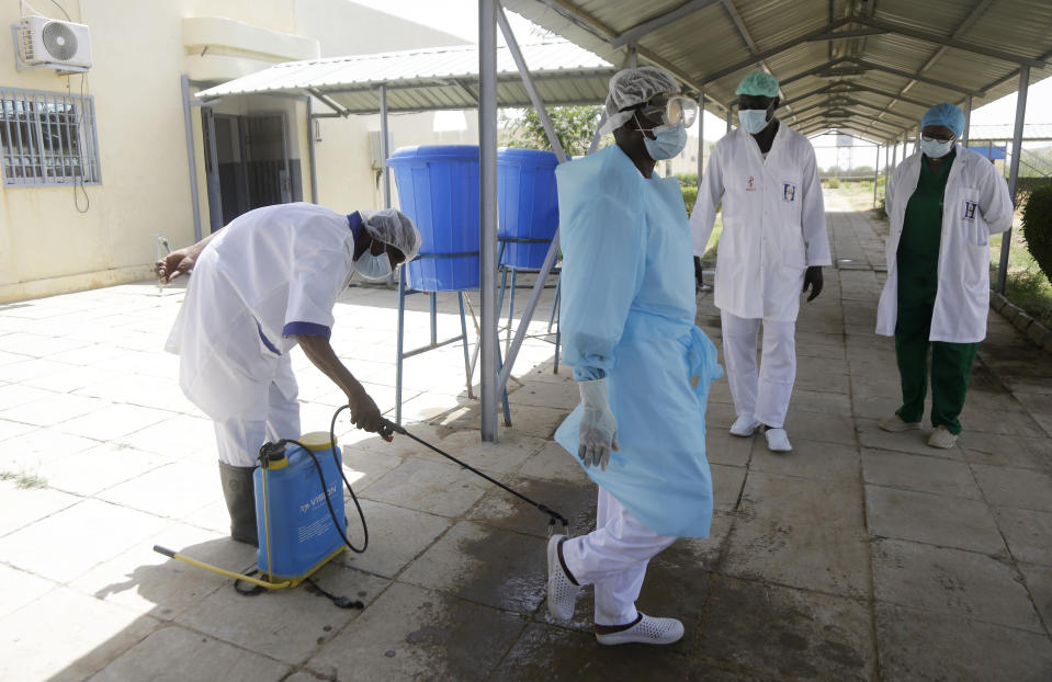 Medical personnel spray disinfectant outside the ward where COVID-19 patients are receiving treatment, at the Farcha provincial hospital in N'Djamena, Chad, Friday April 30, 2021. While the world's wealthier nations have stockpiled coronavirus vaccines for their citizens, many poorer countries are scrambling to secure enough doses, and some, like Chad, have yet to receive any. (AP Photo/Sunday Alamba)