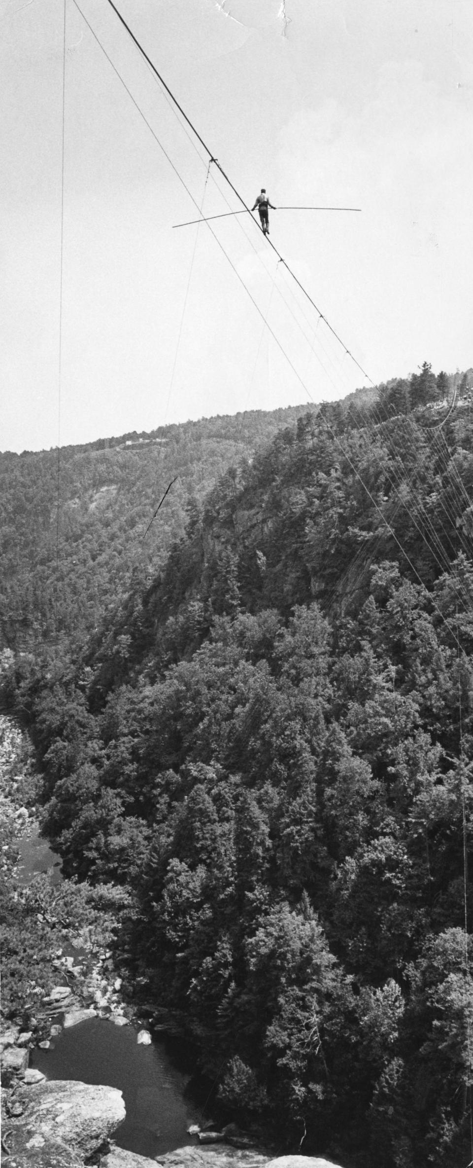 Karl Wallenda, perched hundreds of feet in air, walks on a tightrope over Tallulah Gorge in Georgia on July 18, 1970. Crowds lined cliffs on both sides of the famed chasm to see the aerialist's stunt. (Dwight Ross Jr./Atlanta Journal-Constitution via AP)