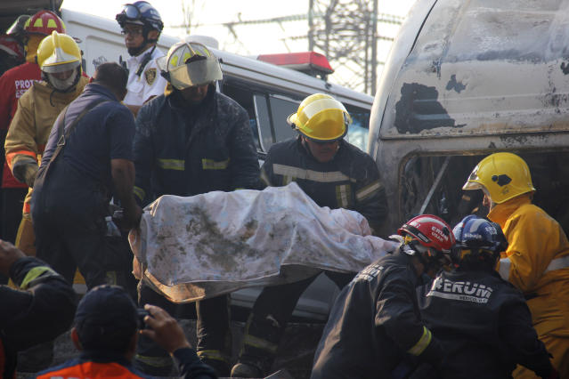 Firefighters remove a body from a home that was destroyed when a gas tanker truck exploded on a nearby highway in the Mexico City suburb of Ecatepec early Tuesday, May 7, 2013. The blast killed and injured dozens, according to the Citizen Safety Department of Mexico State. Officials did not rule out the possibility the death toll could rise as emergency workers continued sifting through the charred remains of vehicles and homes built near the highway on the northern edge of the metropolis. (AP Photo/Gabriela Sanchez)