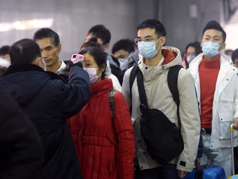 Workers use infrared thermometers to check the temperature of passengers arriving from Wuhan at a train station in Hangzhou in eastern China's Zhejiang Province: Chinatopix via AP