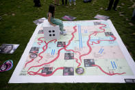"""Gabriella, the seven year old daughter of imprisoned British-Iranian woman Nazanin Zaghari-Ratcliffe sits on a die on a giant snakes and ladders board in Parliament Square, London, to show the """"ups and downs"""" of Zaghari-Ratcliffe's case to mark the 2,000 days she has been detained in Iran, Thursday, Sept. 23, 2021. Zaghari-Ratcliffe was originally sentenced to five years in prison after being convicted of plotting the overthrow of Iran's government, a charge that she, her supporters and rights groups deny. While employed at the Thomson Reuters Foundation, the charitable arm of the news agency, she was taken into custody at the Tehran airport in April 2016 as she was returning home to Britain after visiting family. (AP Photo/Matt Dunham)"""