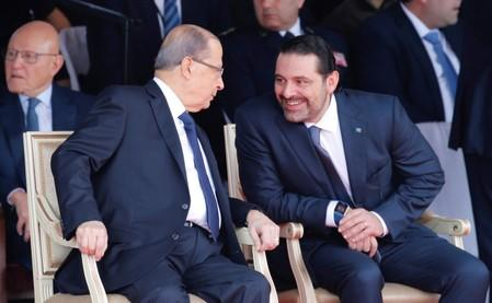 FILE PHOTO: Saad al-Hariri, who announced his resignation as Lebanon's prime minister from Saudi Arabia reacts as he talks with Lebanese President Michel Aoun while attending a military parade to celebrate the 74th anniversary of Lebanon's independence in