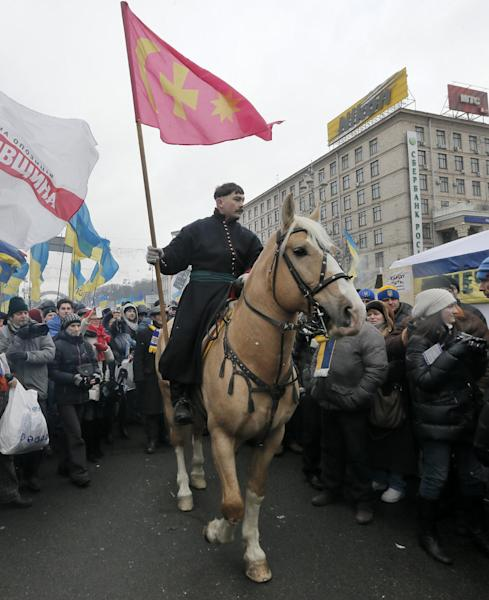 A man dressed as a Cossack on a horse parades through the street during a Pro-European Union rally in Independence Square, Kiev, Ukraine, Sunday, Dec. 8, 2013. The third week of protests continue Sunday with an estimated 200,000 Ukrainians occupying central Kiev to denounce President Viktor Yanukovych's decision to turn away from Europe and align this ex-Soviet republic with Russia. (AP Photo/Efrem Lukatsky)