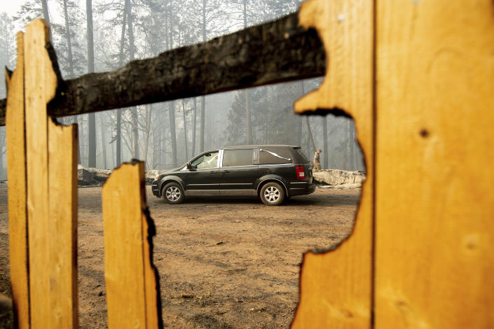 <p>A sheriff's deputy searches for human remains at a residence destroyed by the Camp Fire on Nov. 10, 2018, in Paradise, Calif. The hearse carries multiple victims. (Photo: Noah Berger/AP) </p>