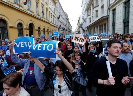 """Demonstrators hold up a banner saying """"Veto"""" during a rally against a new law passed by Hungarian parliament which could force the Soros-founded Central European University out of Hungary"""
