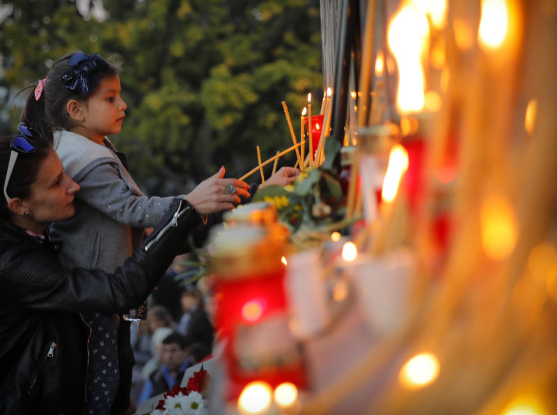 A child lights candles next to a portrait of slain television reporter Viktoria Marinova during a vigil at the Liberty Monument in Ruse, Bulgaria, Monday, Oct. 8, 2018. Bulgarian police are investigating the rape, beating and slaying of a female television reporter whose body was dumped near the Danube River after she reported on the possible misuse of European Union funds in Bulgaria. (AP Photo/Vadim Ghirda)