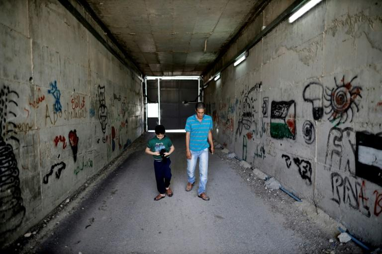 Palestinian Omar Hajajla walks with his son through the tunnel connecting their home in Jerusalem to al-Walajah, their village in the occupied West Bank (AFP Photo/THOMAS COEX)