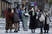 People wearing protective masks to help curb the spread of the coronavirus visit Asakusa district Tuesday, Nov. 24, 2020, in Tokyo. The Japanese capital confirmed more than 180 new coronavirus cases on Tuesday. (AP Photo/Eugene Hoshiko)