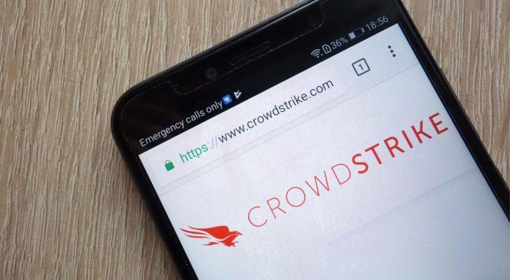 Image of Crowdstrike (CRWD) logo on a mobile phone lying on a wooden table