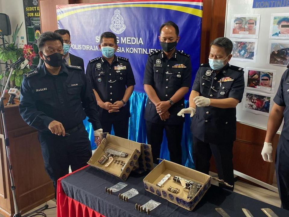 Sabah police commissioner Datuk Hazani Ghazali (left) shows the pistols used by the suspects in the shootout yesterday morning. — Picture by Julia Chan