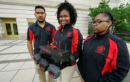 Students Iris Harris and Domonique Dumas with their mentor Kevin Sarran display their Griffin scout robot that will be used by police during a demonstration of police capabilities near the site of the Republican National Convention in Cleveland, Ohio July 14, 2016. REUTERS/Rick Wilking