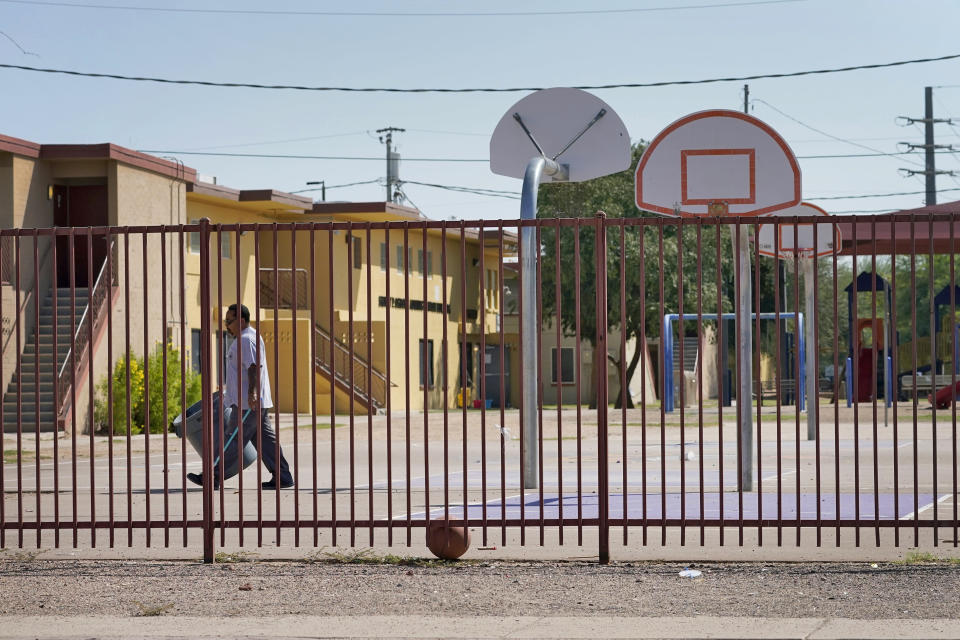 A man walks across a vacant basketball court outside pubic housing, Monday, Sept. 13, 2021, in Phoenix. Soaring temperatures are making it harder to live in the United States' already hot, fast growing desert areas. Heat dangers are even more pronounced in poor and racially and ethnically diverse communities in the West's burgeoning desert cities and counties, where people don't have enough protection against heat waves. (AP Photo/Matt York)
