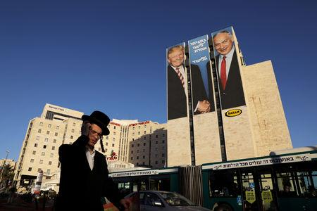FILE PHOTO: A man walks past a Likud election campaign billboard, depicting U.S. President Donald Trump shaking hands with Israeli Prime Minister Benjamin Netanyahu, in Jerusalem February 4, 2019. REUTERS/Ammar Awad/File Photo