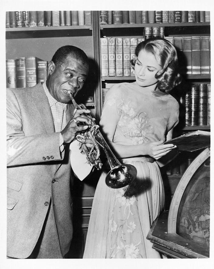 <p>Kelly looks on at famous trumpeter Louis Armstrong, while on the set of <em>High Society</em> in 1956. The musician appeared in both the beginning and end of the film, performing songs in both scenes. </p>
