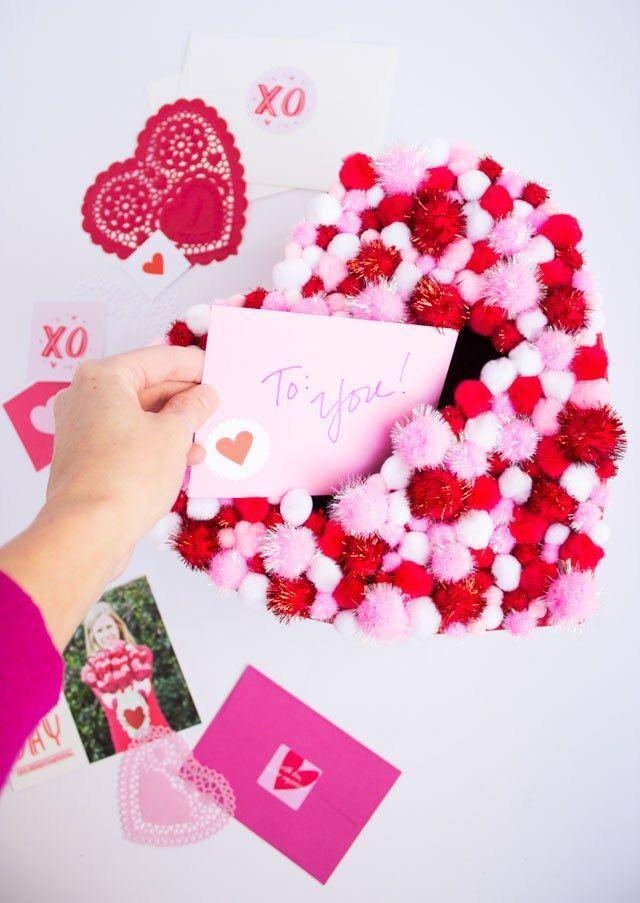 """<p>Who doesn't need more fuzzy little pom-poms in their lives? This DIY Valentine's Box is just adorable!</p><p><strong>Get the tutorial at</strong><strong> <a href=""""https://designimprovised.com/2016/02/diy-pom-pom-heart-valentine-card-holder-box.html"""" rel=""""nofollow noopener"""" target=""""_blank"""" data-ylk=""""slk:Design Improvised."""" class=""""link rapid-noclick-resp"""">Design Improvised.</a></strong></p><p><a class=""""link rapid-noclick-resp"""" href=""""https://www.amazon.com/Pieces-Valentines-Assorted-Glitter-Decorations/dp/B082FHMJ2R/?tag=syn-yahoo-20&ascsubtag=%5Bartid%7C2164.g.35119968%5Bsrc%7Cyahoo-us"""" rel=""""nofollow noopener"""" target=""""_blank"""" data-ylk=""""slk:SHOP POM-POMS"""">SHOP POM-POMS</a></p>"""