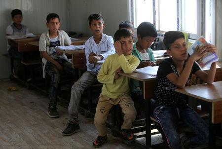 Children of Iraqi Kawliya group (known as Iraqi gypsies) attend a class at a school in al-Zuhoor village near the southern city of Diwaniya, Iraq April 16, 2018. Picture taken April 16, 2018.  REUTERS/Alaa Al-Marjani