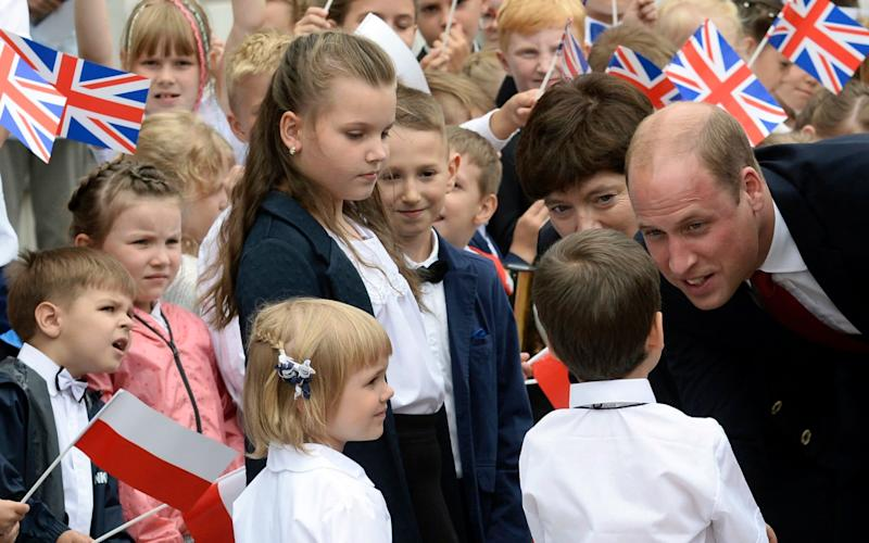 Children welcome Britain's Prince William, right, in front of the presidential palace - Credit: AP Photo/Alik Keplicz
