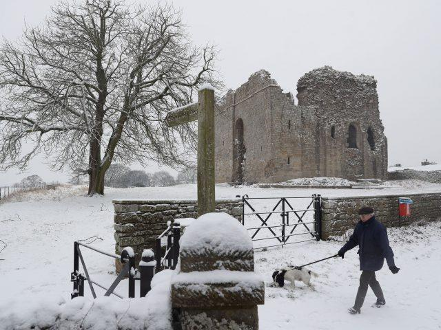 A man walks his dog in the snow by Bowes Castle in County Durham (Owen Humphreys/PA)