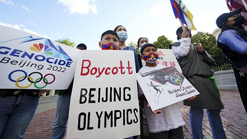 Group of people holding protest signs that say 'Boycott Beijing Olympics' and 'Genocide Beijing 2022.'