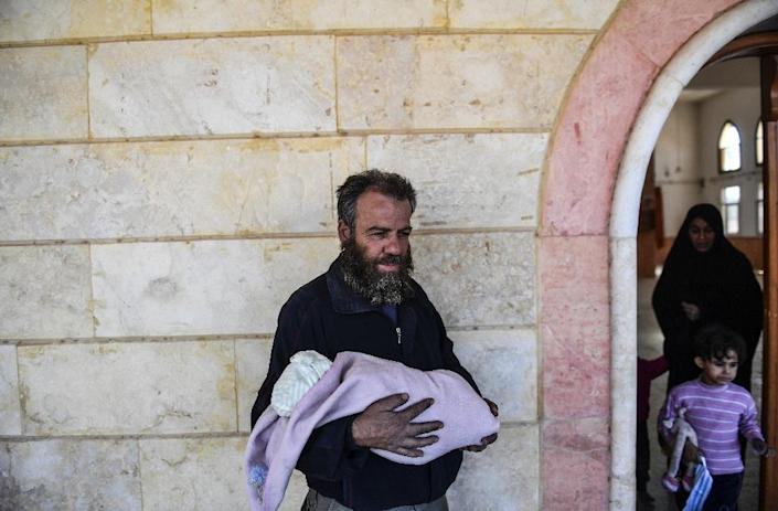 A man who was used as human shield by Islamic State group fighters holds a baby after fleeing from Raqa (AFP Photo/BULENT KILIC)