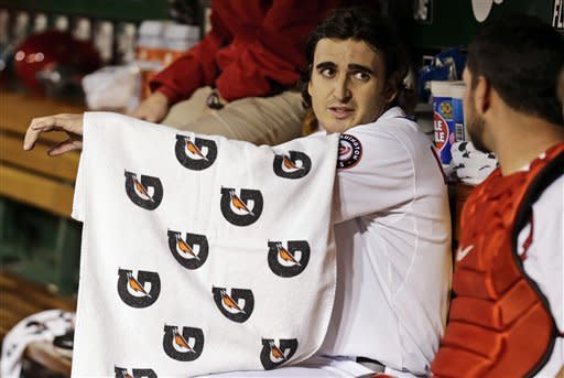 Washington Nationals starting pitcher John Lannan, left, wraps his arm with a towel during the second inning of the second baseball game of a doubleheader against the Los Angeles Dodgers at Nationals Park, Wednesday, Sept. 19, 2012, in Washington. (AP Photo/Alex Brandon)