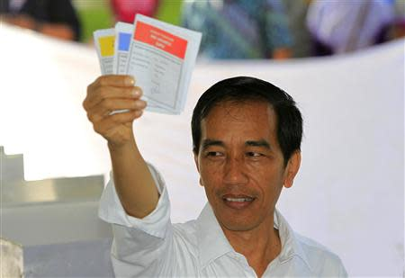 Jakarta governor and presidential candidate from the Indonesian Democratic Party-Struggle (PDI-P) party, Joko Widodo, shows his ballot paper during voting in the parliamentary elections in Jakarta April 9, 2014. REUTERS/Beawiharta