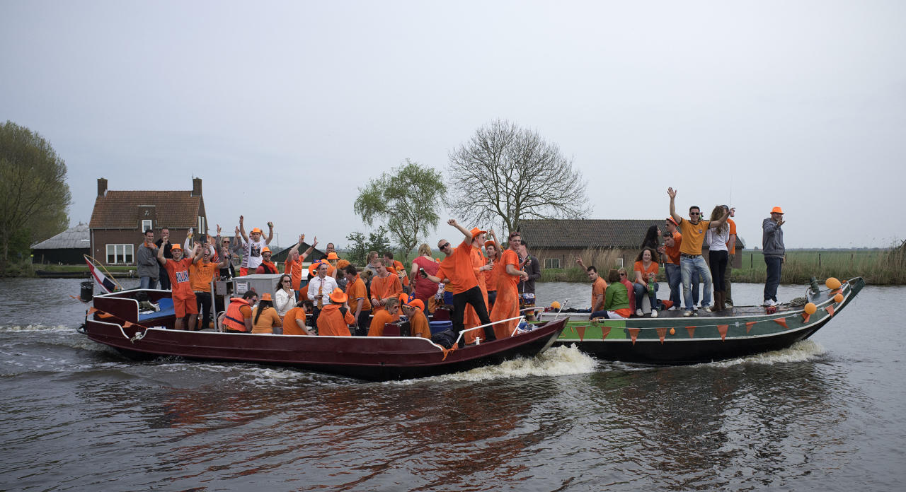 Orange-clad partygoers dance to the music in their boats on Amstel river in the village of Nes aan de Amstel, on their way back from Amsterdam, Monday April 30, 2012. The Dutch celebrate Queen's Day, a Dutch national holiday marking the birthday of the Queen's mother. (AP Photo/Peter Dejong)