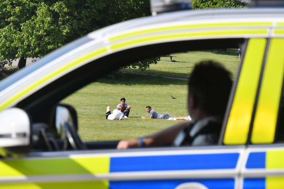"""Police officers look at people relaxing in the sunshine on Primrose Hill in London on May 7, 2020 as life continues in Britain under a nationwise lockdown to slow the spread of the novel coronavirus. - British Prime Minister Boris Johnson told senior ministers on May 7 the government would adopt """"maximum caution"""" as it moves towards a relaxation of lockdown measures imposed to combat the coronavirus outbreak. (Photo by JUSTIN TALLIS / AFP) (Photo by JUSTIN TALLIS/AFP via Getty Images)"""
