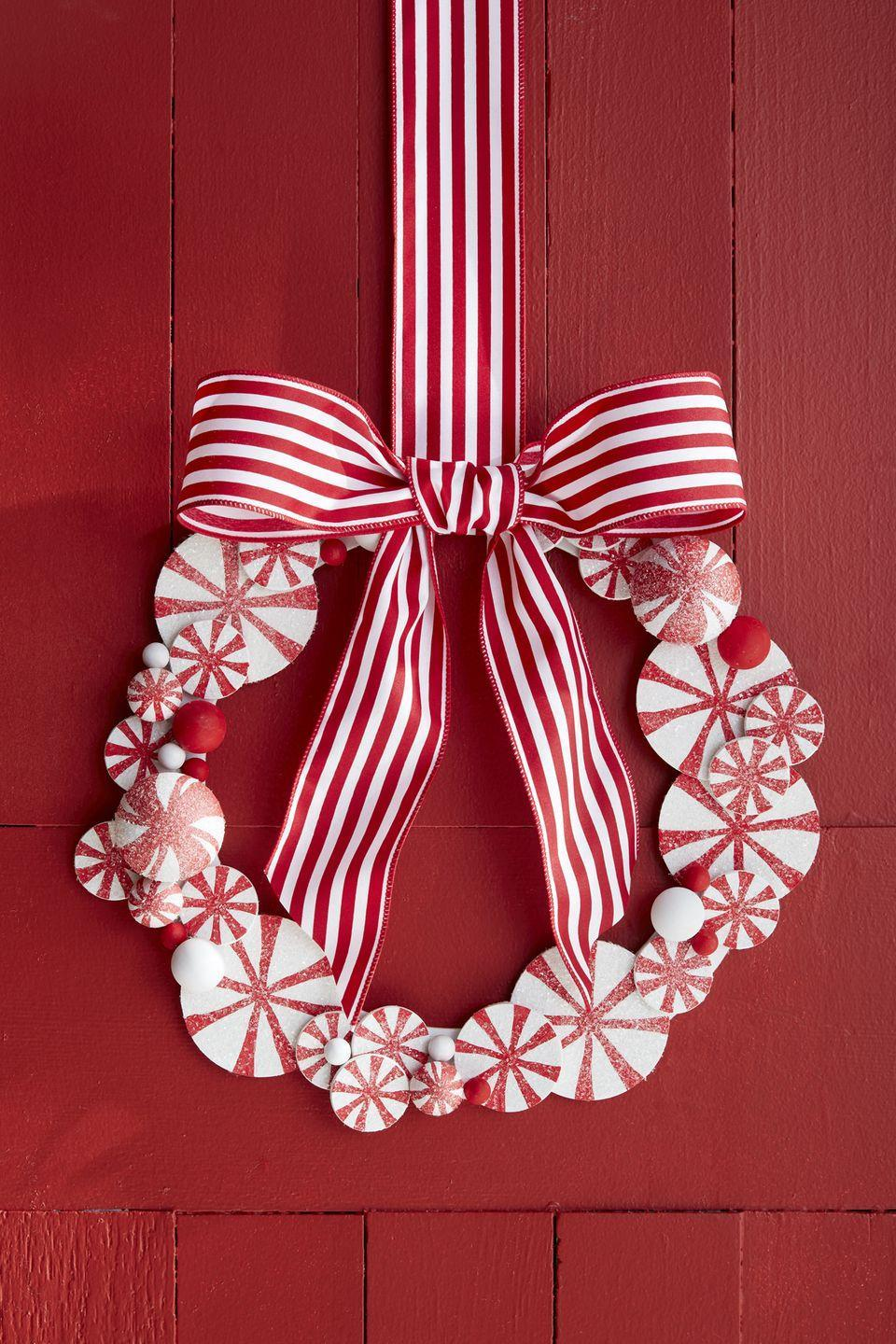 <p>This two-toned wreath, made with painted wooden rounds, striped ribbon, and pom poms, will pop against any front door color (especially red!). </p>