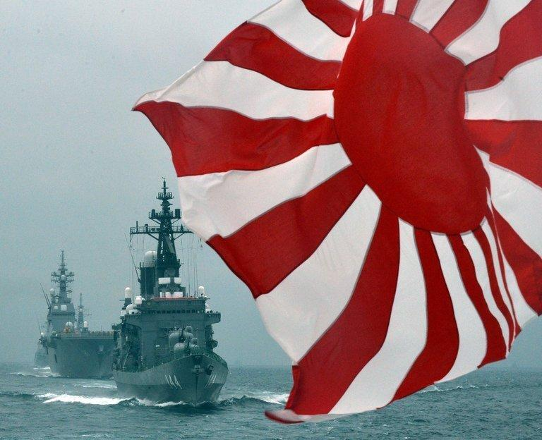 The flag of the Japanese Maritime Self-Defense Force flutters in the wind during a fleet review on October 14, 2012