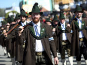 Men in traditional costumes carry rifles as they take part in a parade as part of the opening of the 186th 'Oktoberfest' beer festival in Munich, Germany, Saturday, Sept. 21, 2019. (AP Photo/Matthias Schrader)